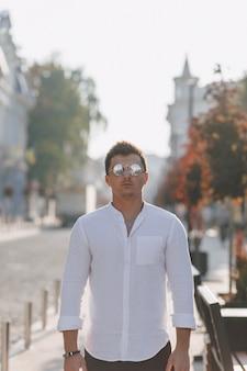Jonge stijlvolle man in een shirt lopen in een europese straat op een zonnige dag