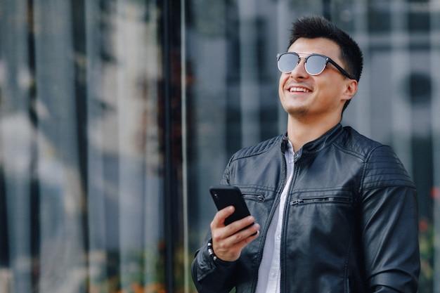 Jonge stijlvolle man in glazen in zwart lederen jas met telefoon op glas