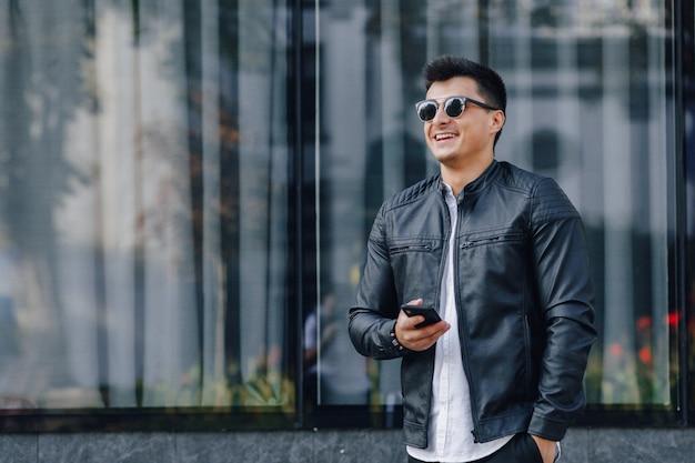 Jonge stijlvolle man in glazen in zwart lederen jas met telefoon