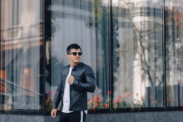 Jonge stijlvolle man in glazen in zwart lederen jas op glas