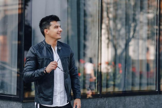 Jonge stijlvolle man in glazen in zwart lederen jas op glazen oppervlak