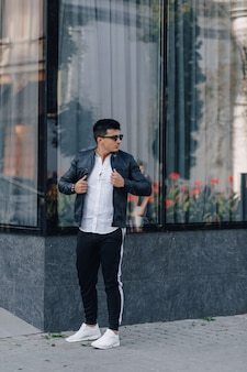 Jonge stijlvolle man in glazen in zwart lederen jas