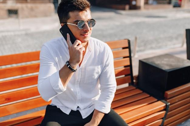 Jonge stijlvolle man in shirt met telefoon op bankje op zonnige warme dag buitenshuis