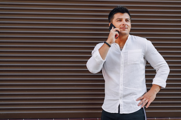 Jonge stijlvolle man in shirt praten via de telefoon op eenvoudige oppervlak