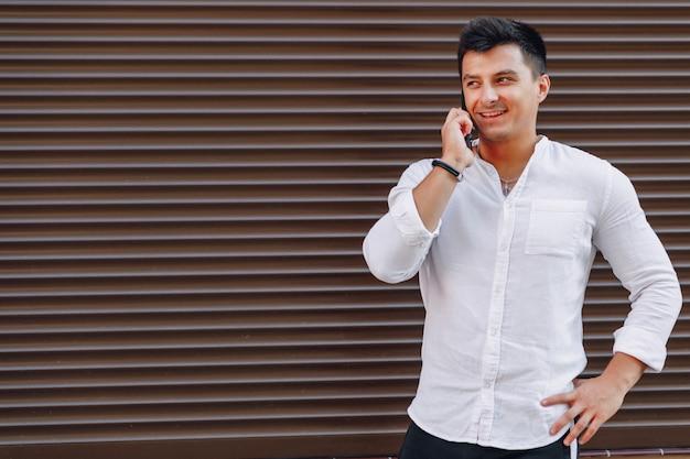 Jonge stijlvolle man in shirt praten via de telefoon