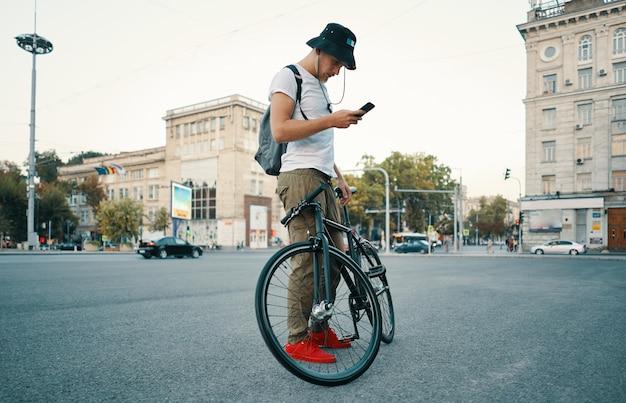 Jonge stijlvolle man texting op de telefoon terwijl opzij fiets.
