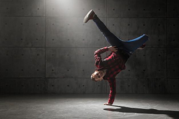 Jonge stijlvolle mannelijke breakdancer poseren in studio