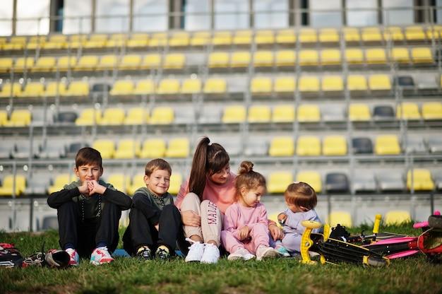 Jonge stijlvolle moeder met vier kinderen zittend op gras tegen stadion. sportfamilie brengt vrije tijd buitenshuis door met scooters en skates.