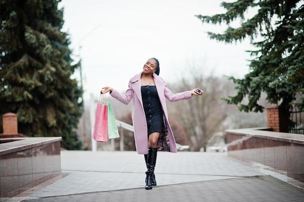 Jonge stijlvolle mooie afro-amerikaanse vrouw in straat, het dragen van mode outfit jas met boodschappentassen en mobiele telefoon bij handen.