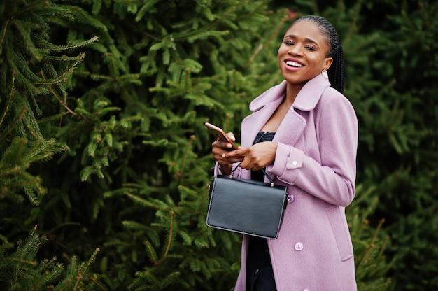 Jonge stijlvolle mooie afro-amerikaanse vrouw in straat in de buurt van pijnbomen, het dragen van mode outfit jas, met handtas en mobiele telefoon bij handen.