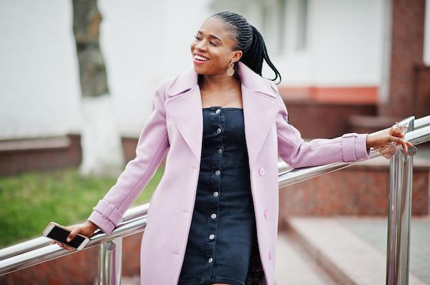 Jonge stijlvolle mooie afro-amerikaanse vrouw in straat, mode outfit jas dragen, met mobiele telefoon.