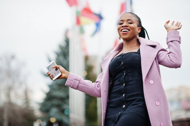 Jonge stijlvolle mooie afro-amerikaanse vrouw in straat, mode outfit jas dragen, tegen vlaggen van verschillende landen van de wereld, met mobiele telefoon bij de hand.