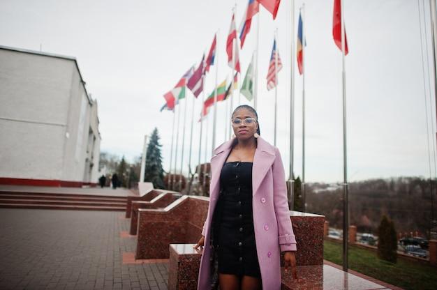 Jonge stijlvolle mooie afro-amerikaanse vrouw in straat, mode outfit jas en bril dragen, tegen vlaggen van verschillende landen van de wereld.