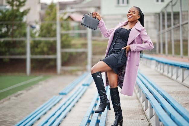 Jonge stijlvolle mooie afro-amerikaanse vrouw in straat op de tribunes van het stadion, het dragen van mode outfit jas, met handtas.
