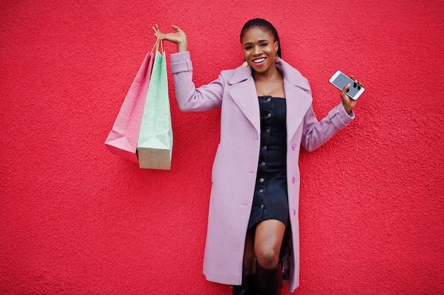 Jonge stijlvolle mooie afro-amerikaanse vrouw tegen rode muur achtergrond, het dragen van mode outfit jas met boodschappentassen en mobiele telefoon bij handen.