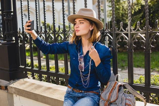 Jonge stijlvolle mooie vrouw die een selfie neemt, gekleed in denimoverhemd en spijkerbroek