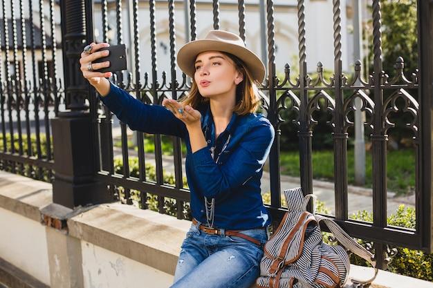 Jonge stijlvolle mooie vrouw een kus verzenden door haar telefoon, gekleed in denimoverhemd en spijkerbroek