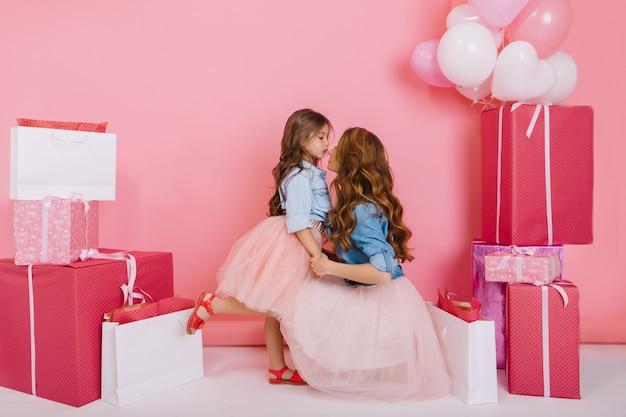 Jonge stijlvolle mooie vrouw feliciteert dochter in weelderige rok op verjaardag met haar bij de handen op roze achtergrond. het meisje dat op één been staat, bedankt haar schattige moeder voor geschenken op vakantie