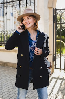 Jonge stijlvolle mooie vrouw glimlachend en praten over haar telefoon, gekleed in donkerblauwe jas en spijkerbroek