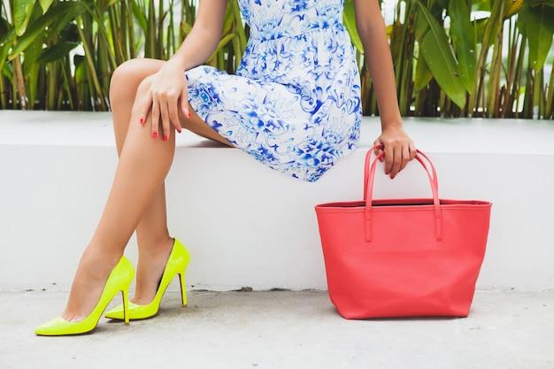 Jonge stijlvolle mooie vrouw in blauwe bedrukte jurk, rode tas, modieuze outfit, trendy kleding, zittend, gele schoenen met hoge hakken, accessoires, benen close-up, details