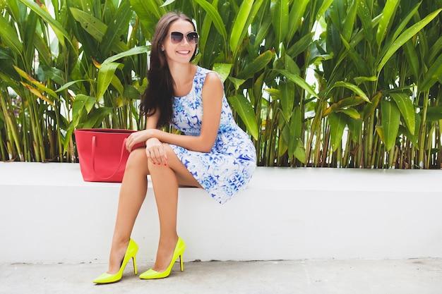 Jonge stijlvolle mooie vrouw in blauwe bedrukte jurk, rode tas, zonnebril, vrolijke stemming, modieuze outfit, trendy kleding, glimlachen, zittend, zomer, gele schoenen met hoge hakken, accessoires