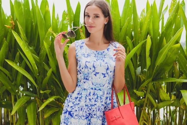 Jonge stijlvolle mooie vrouw in blauwe bedrukte jurk, rode tas, zonnebril, vrolijke stemming, modieuze outfit, trendy kleding, glimlachen, zomer, accessoires