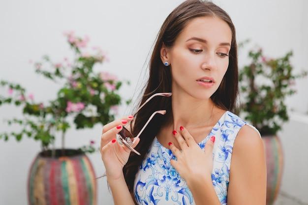 Jonge stijlvolle mooie vrouw in blauwe gedrukte jurk, zonnebril, gelukkig humeur, mode-outfit, trendy kleding, glimlachen, zomer, accessoires