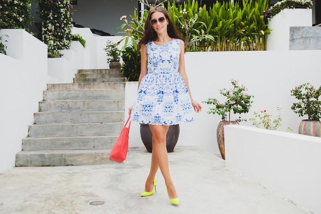 Jonge stijlvolle mooie vrouw in blauwe jurk met print, rode tas, zonnebril, vrolijke stemming, mode-outfit, trendy kleding, glimlachen, accessoires, speels, wandelen, zomer, lopend op gele schoenen met hoge hak