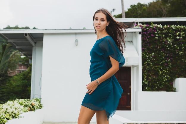 Jonge stijlvolle mooie vrouw in blauwe jurk, zomer modetrend, vakantie, tuin, tropisch hotelterras, glimlachen, wandelen