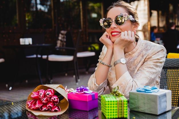 Jonge stijlvolle mooie vrouw in mode zonnebril zit in café met cadeautjes