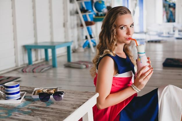 Jonge stijlvolle mooie vrouw in zee café, cocktail smoothie drinken, zonnebril, flirterige, resortstijl, modieuze outfit, glimlachen, mariene kleuren jurk