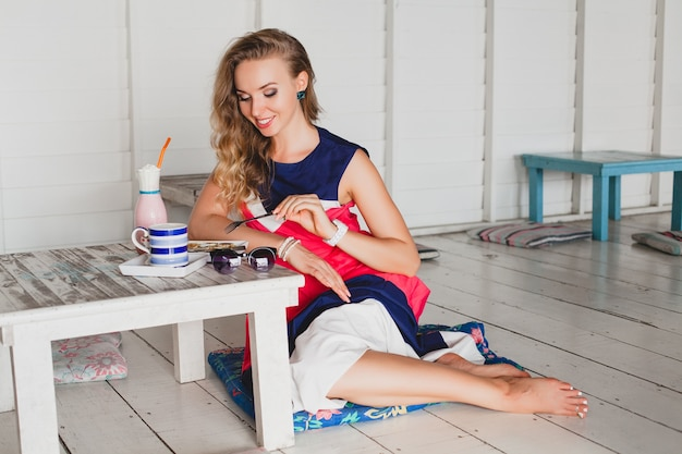 Jonge stijlvolle mooie vrouw in zee café, pannenkoeken eten, cocktail smoothie, zonnebril, flirterige, resortstijl, modieuze outfit, glimlachen, mariene kleuren jurk