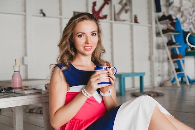 Jonge stijlvolle mooie vrouw in zee café, warme cappuccino drinken, resortstijl, modieuze outfit, glimlachen, mariene kleuren jurk, zittend op de vloer, vakantie, ontspannen