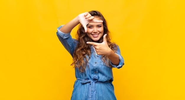 Jonge stijlvolle mooie vrouw op gele achtergrond