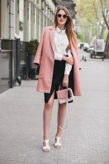 Jonge stijlvolle mooie vrouw wandelen in de straat, roze jas dragen