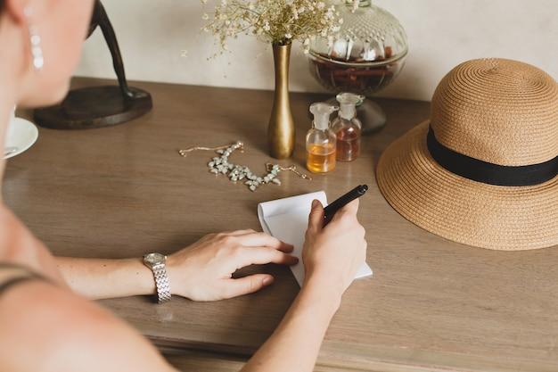 Jonge stijlvolle mooie vrouw zittend aan tafel in de hotelkamer van het resort, een brief schrijven, pen vasthouden, strooien hoed, vintage stijl, handen close-up, details, accessoires, reisdagboek