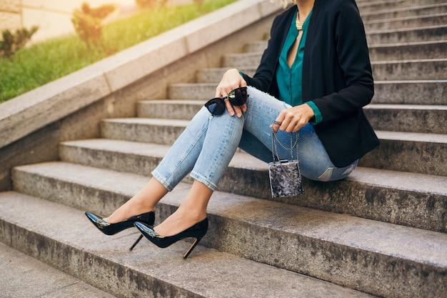 Jonge stijlvolle mooie vrouw zittend in de straat, spijkerbroek, zwarte jas, groene blouse, zonnebril dragen