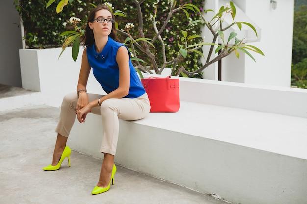 Jonge stijlvolle mooie vrouw, zomer modetrend, blauwe blouse, rode tas, bril, tropische villa resort, vakantie, flirterig, lange slanke benen, broek, gele schoenen, hakken