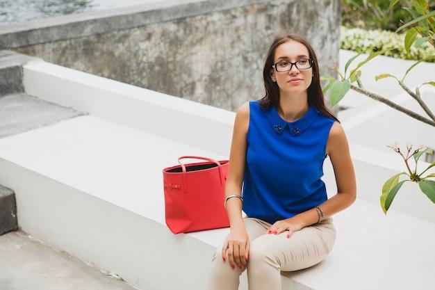Jonge stijlvolle mooie vrouw, zomer modetrend, blauwe blouse, rode tas, bril, tropische villa resort, vakantie, flirterig