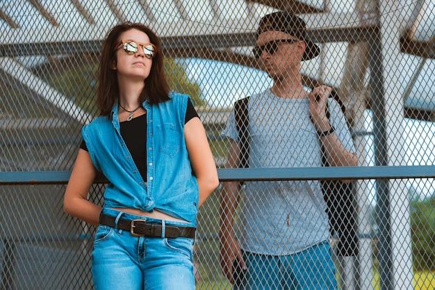 Jonge stijlvolle paar hipsters zonnebril, jongen meisje stedelijke ruimte gescheiden kooi hek. concept relatie tussen man vrouw, meningsverschillen, misverstanden conflict, depressie, verschillende kanten