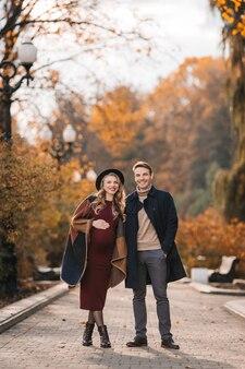 Jonge stijlvolle paar verliefd op een herfst stadspark gelukkig stijlvolle man en mooie zwangere vrouw i...