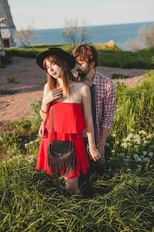 Jonge stijlvolle paar verliefd op platteland, indie hipster bohemien stijl, weekendvakantie, zomer outfit, rode jurk, groen gras, hand in hand, glimlachen