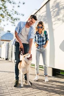 Jonge stijlvolle paar wandelen met de hond in de straat. man en vrouw gelukkig samen met husky-ras,