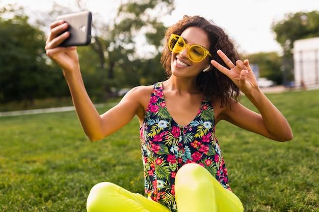 Jonge stijlvolle positieve zwarte vrouw selfie foto luisteren naar muziek op draadloze oortelefoons met plezier in park, zomer fashion stijl, kleurrijke hipster outfit
