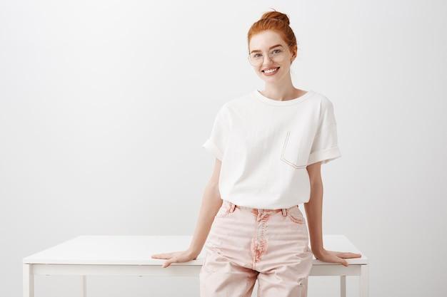 Jonge stijlvolle roodharige meisje glimlachen, leunend op tafel