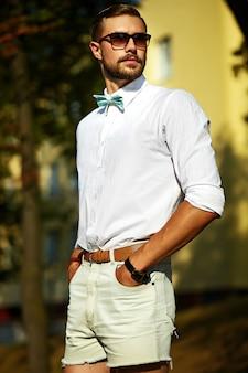 Jonge stijlvolle sexy knappe model man in casual doek levensstijl in de straat in glazen