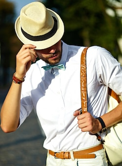 Jonge stijlvolle sexy knappe model man toerist in casual doek levensstijl in de straat in hoed met tas
