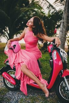 Jonge stijlvolle sexy mooie vrouw in roze jurk op scooter motor