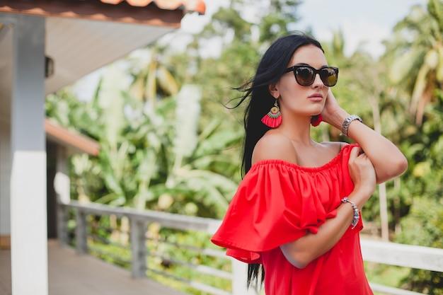 Jonge stijlvolle sexy vrouw in rode zomerjurk staande op terras in tropisch hotel, palmbomen achtergrond, lang zwart haar, zonnebril, etnische oorbellen, zonnebril, glimlachen