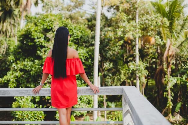 Jonge stijlvolle sexy vrouw in rode zomerjurk staande op terras in tropisch hotel, palmbomen achtergrond, lang zwart haar, zonnebril, etnische oorbellen, zonnebril, verheugen